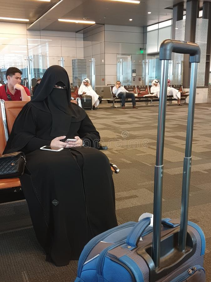 Mulher muçulmana com um telefone celular em suas mãos foto de stock royalty free