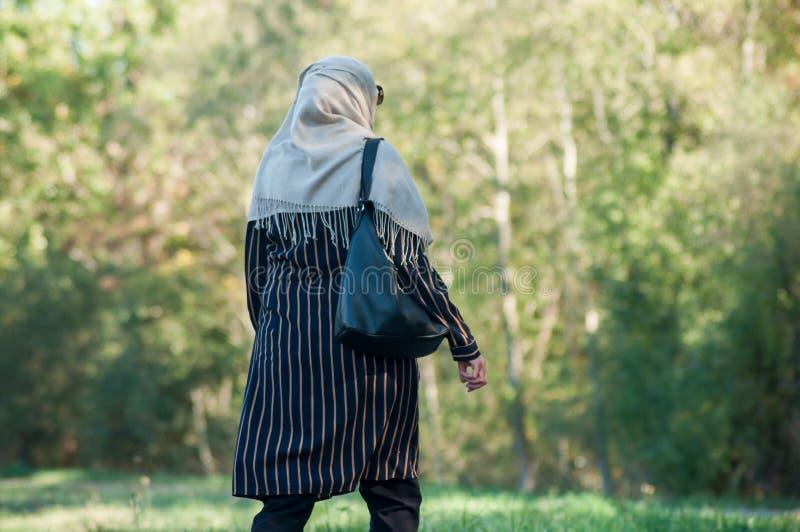 Mulher muçulmana encoberta que anda em público jardim sobre para trás imagens de stock