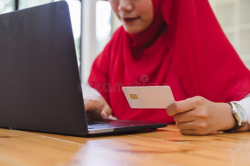 A mulher muçulmana entrega guardar o cartão de crédito e a utilização do portátil para a compra em linha fotografia de stock