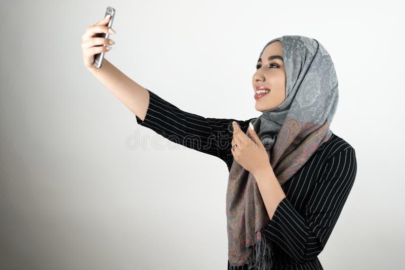 Mulher muçulmana feliz de sorriso bonita nova nos vidros que vestem o hijab do turbante, tiro a do smartphone da terra arrendada  fotografia de stock