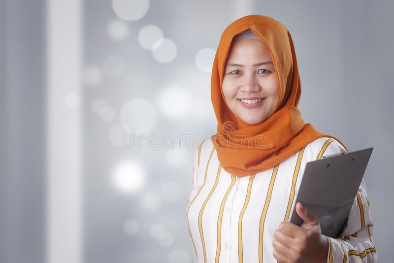 A mulher muçulmana guarda a prancheta fotografia de stock