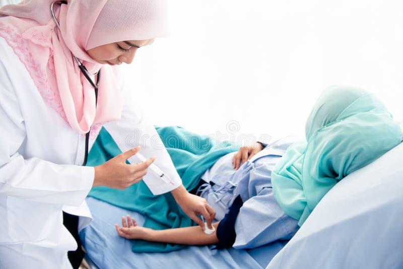 Mulher muçulmana médica que deve ser injetada imagem de stock
