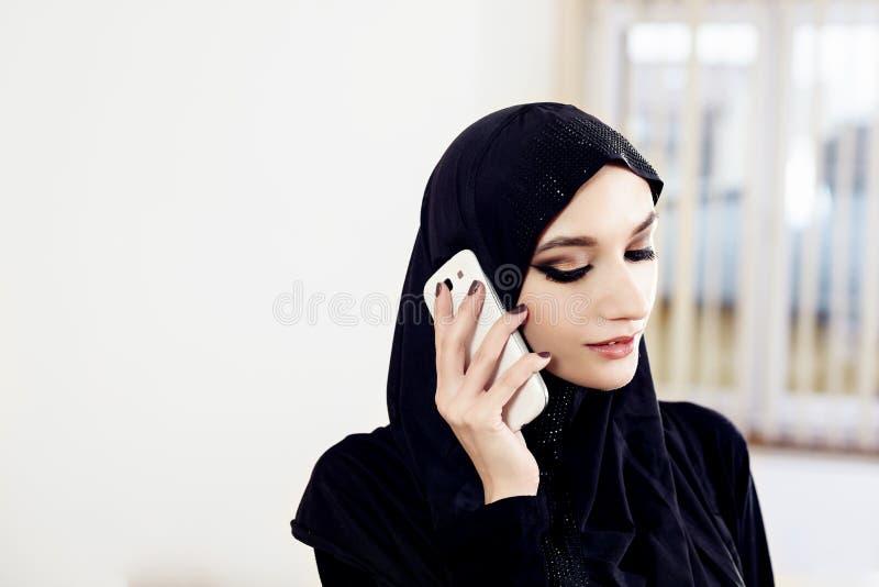 Mulher muçulmana no hijab que fala no telefone celular fotos de stock royalty free