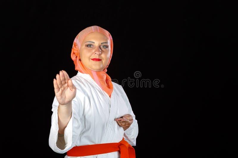 Mulher muçulmana nova no quimono e hijab em exercícios do karaté imagens de stock royalty free