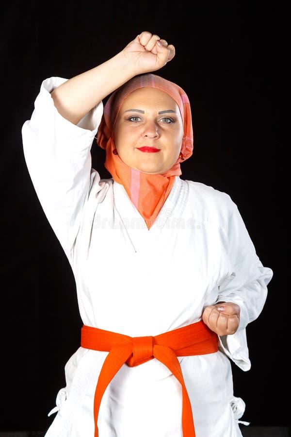 Mulher muçulmana nova no quimono e hijab no treinamento do karaté sobre o fundo preto Close-up do tiro foto de stock royalty free