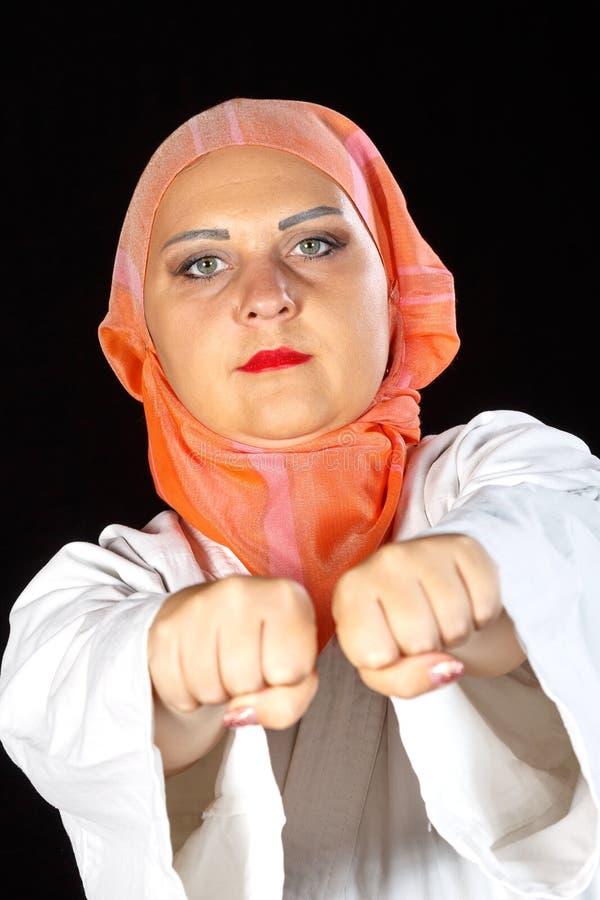 Mulher muçulmana nova no quimono e hijab no treinamento do karaté sobre o fundo preto Close-up do tiro imagens de stock