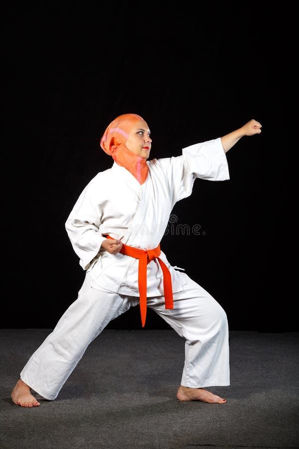 Mulher muçulmana nova no quimono e no xaile durante o treinamento do karaté sobre o fundo preto Tiro no crescimento completo fotos de stock royalty free