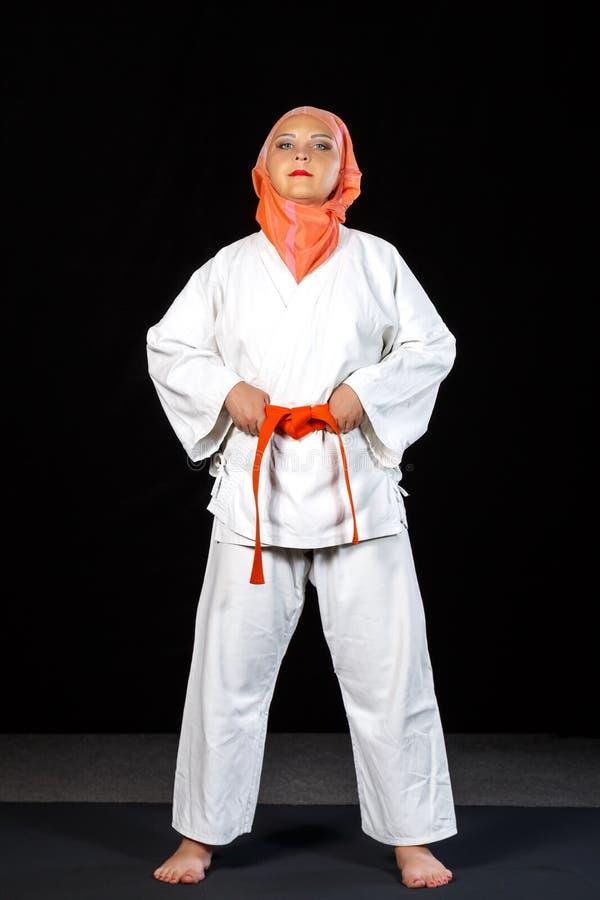 Mulher muçulmana nova no quimono e no xaile durante o treinamento do karaté sobre o fundo preto Tiro no crescimento completo imagem de stock royalty free