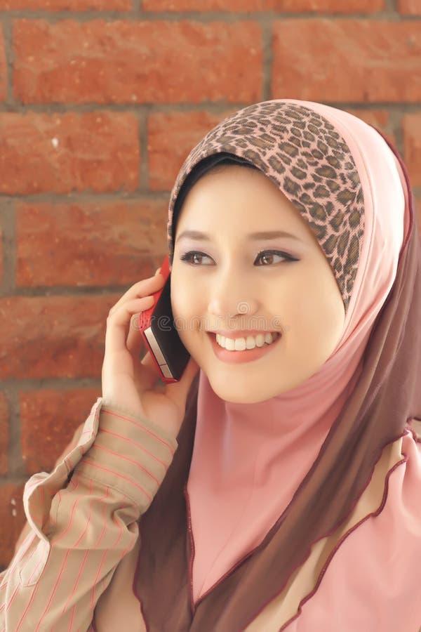 Mulher muçulmana nova que fala no telefone foto de stock royalty free