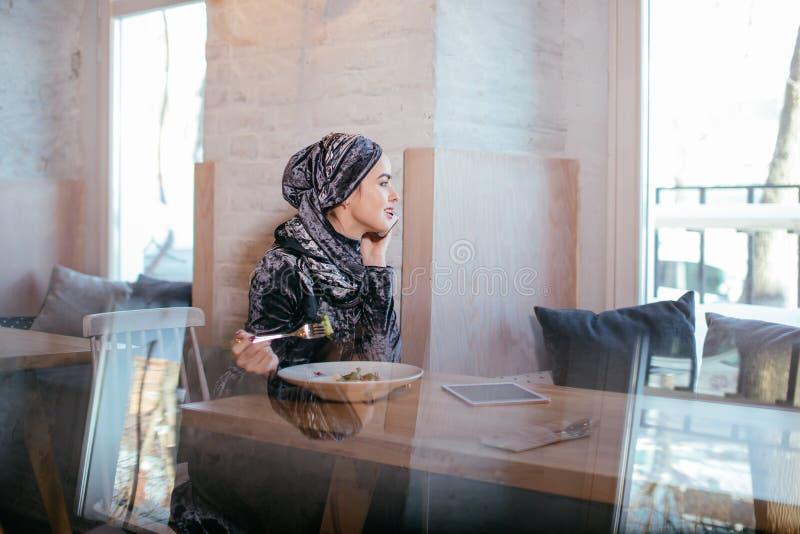 Mulher muçulmana nova que fala no telefone no café e que olha na janela fotografia de stock royalty free