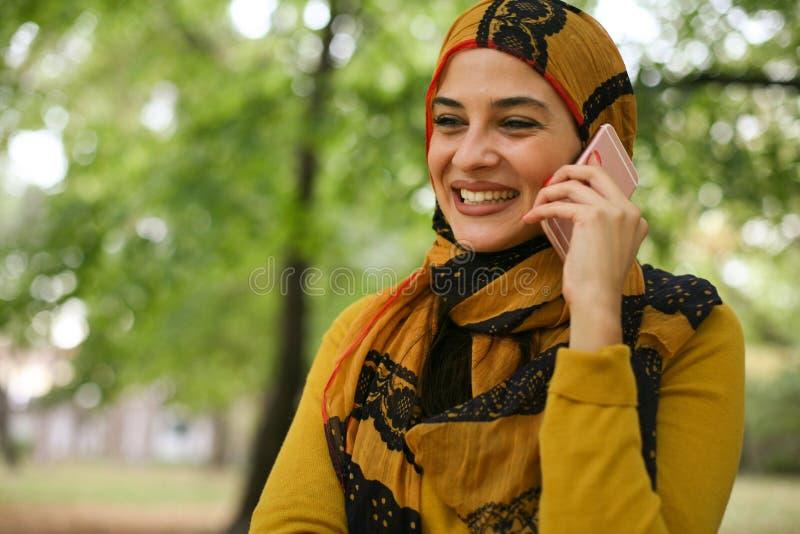 Mulher muçulmana nova que fala no telefone esperto fotografia de stock