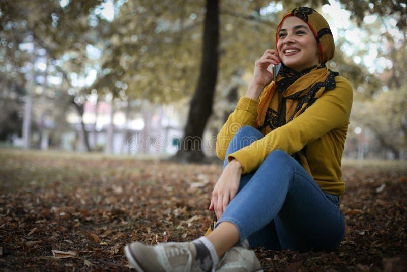 Mulher muçulmana nova que senta-se no parque que fala no telefone esperto fotografia de stock