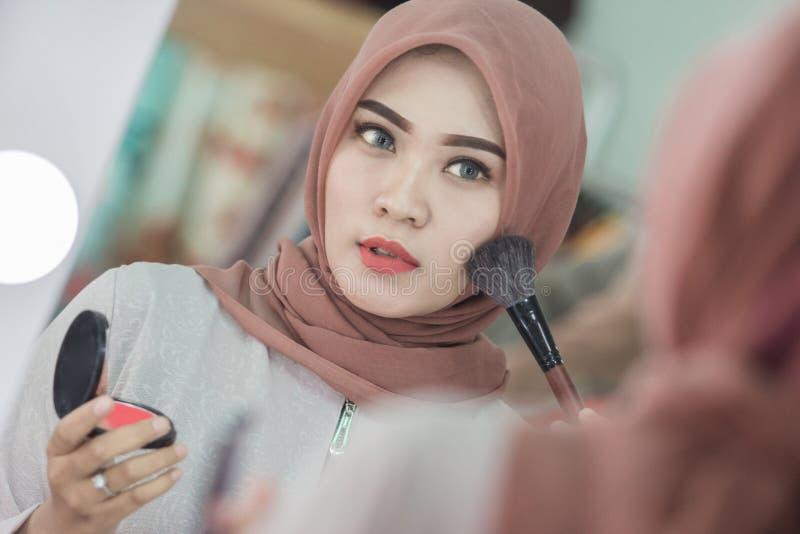 Mulher muçulmana que aplica a composição foto de stock royalty free