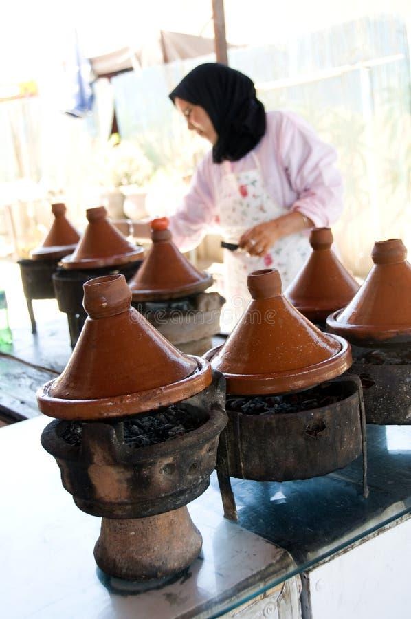 Mulher muçulmana que cozinha o alimento no tagine Marrocos foto de stock