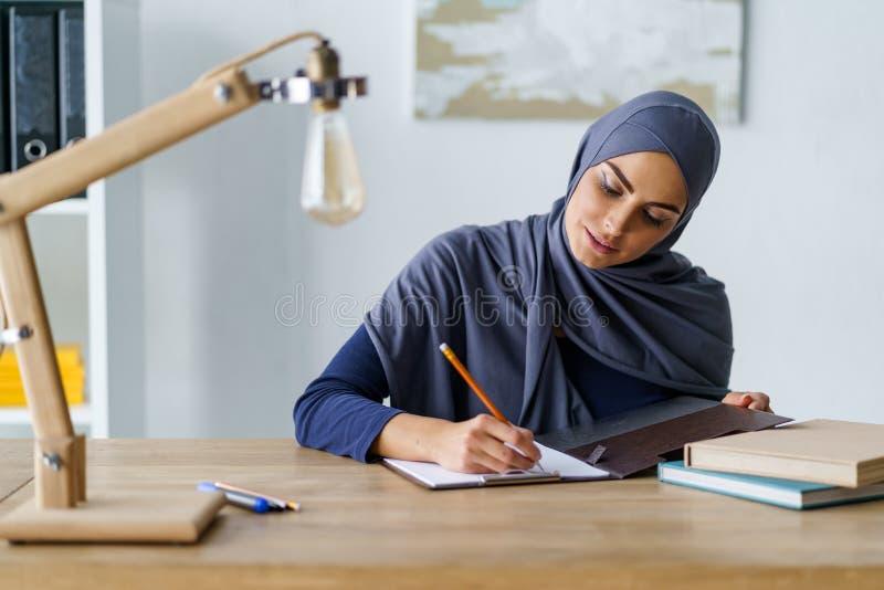 Mulher muçulmana que esboça com lápis fotografia de stock