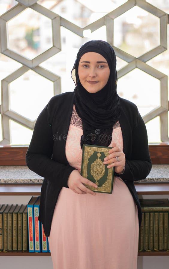 Mulher muçulmana que guarda o Alcorão nas mãos fotos de stock royalty free