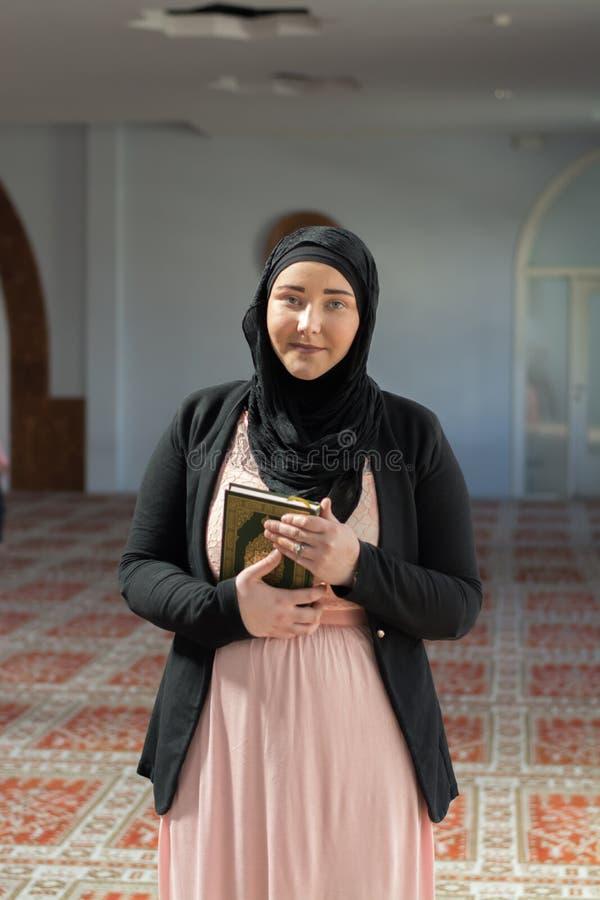 Mulher muçulmana que guarda o Alcorão nas mãos imagem de stock royalty free