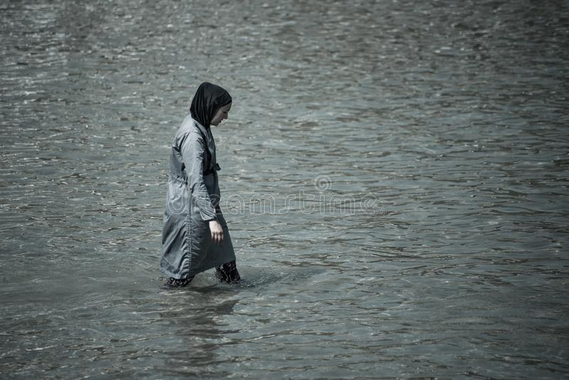 Mulher mu?ulmana que toma uma nadada no mar coberto completamente com a roupa fotos de stock