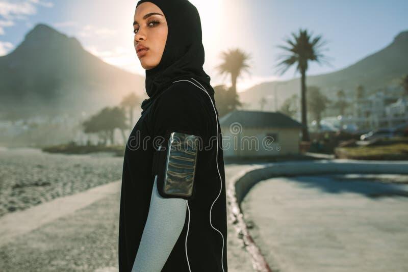Mulher muçulmana que toma uma ruptura após o exercício da manhã foto de stock