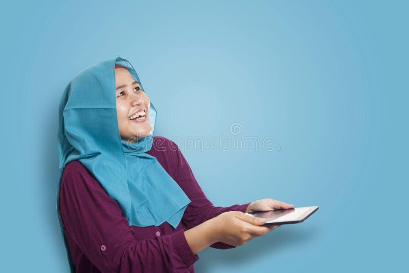 Mulher muçulmana surpreendida ver algo acima de ao usar o telefone imagens de stock