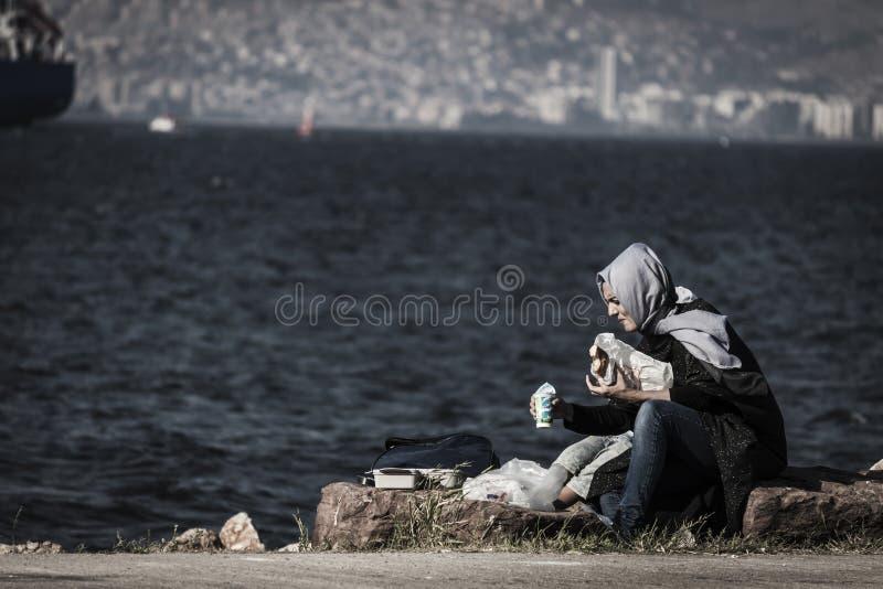 A mulher muçulmana turca está comendo no beira-mar fotos de stock
