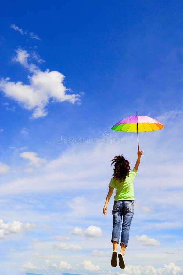 A mulher Multicolor do guarda-chuva salta ao céu imagens de stock royalty free