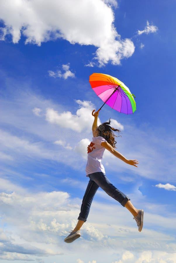 A mulher Multicolor do guarda-chuva salta ao céu foto de stock