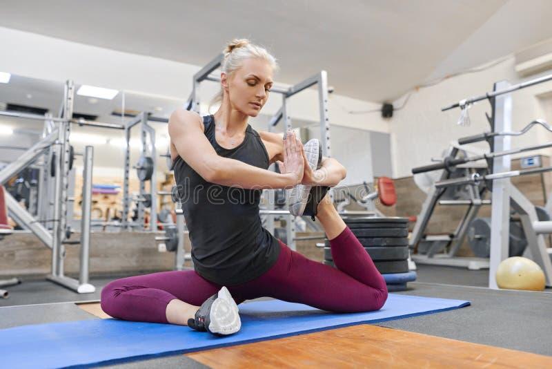 Mulher muscular atlética nova que faz esticando o exercício no gym, ioga praticando da mulher imagens de stock