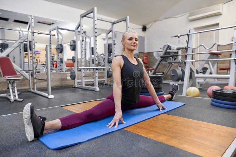 Mulher muscular atlética nova que faz esticando o exercício no gym, ioga praticando da mulher fotos de stock
