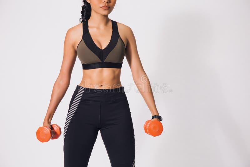 Mulher muscular desportiva nova que mantém pesos isolados sobre o fundo branco Mulher no exercício da roupa do esporte fotos de stock royalty free