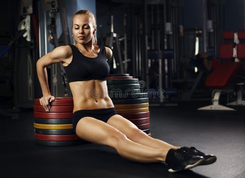 Mulher muscular do ajuste que exercita os músculos da construção fotografia de stock royalty free
