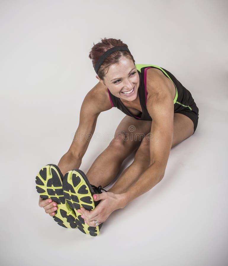 Mulher muscular forte que estica antes do exercício no fundo branco fotos de stock royalty free