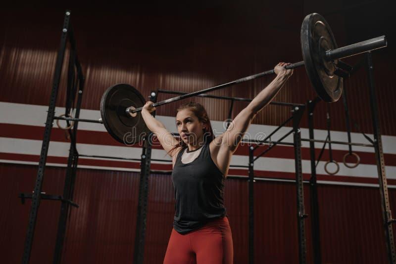 Mulher muscular nova que faz exercícios do halterofilismo no gym do crossfit imagens de stock royalty free