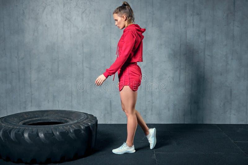 Mulher muscular nova que lança um pneu no treinamento duro com o instrutor pessoal no gym da garagem imagem de stock royalty free