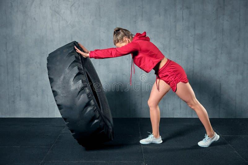 Mulher muscular nova que lança um pneu no treinamento duro com o instrutor pessoal no gym da garagem fotos de stock