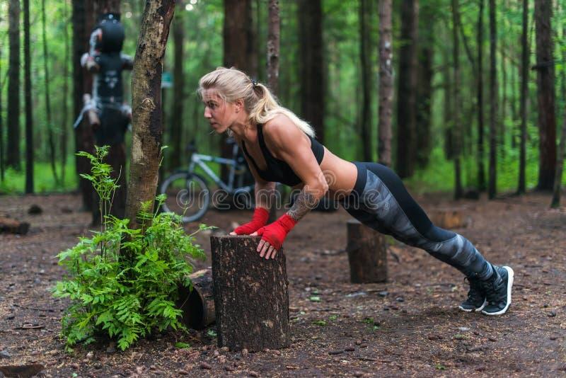 A mulher muscular que faz impulso-UPS na rua do parque dá certo foto de stock