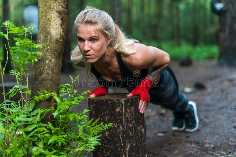 A mulher muscular que faz impulso-UPS na rua do parque dá certo imagem de stock