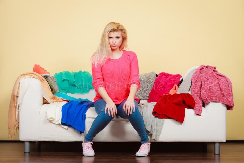 A mulher não conhece o que vestir o assento no sofá fotos de stock