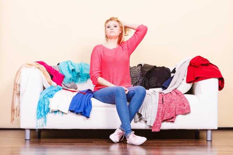 A mulher não conhece o que vestir o assento no sofá imagens de stock royalty free