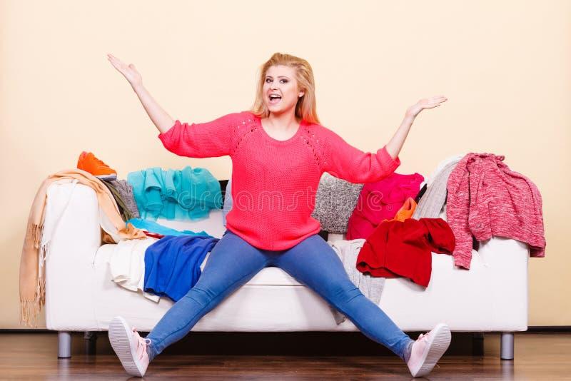 A mulher não conhece o que vestir o assento no sofá imagem de stock royalty free