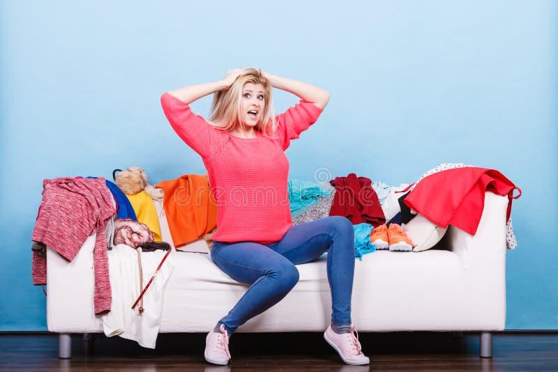 A mulher não conhece o que vestir o assento no sofá fotos de stock royalty free