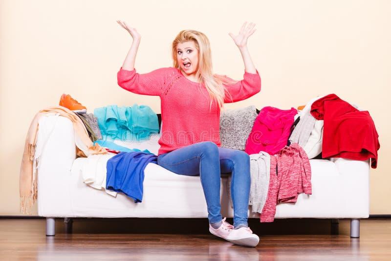 A mulher não conhece o que vestir o assento no sofá imagens de stock