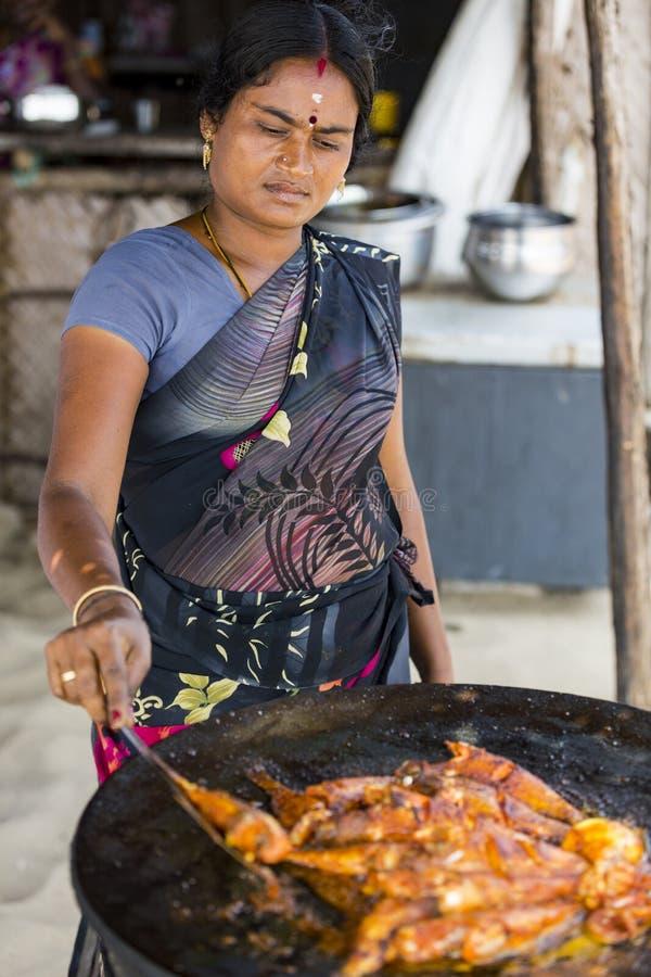 Mulher não identificada que cozinha peixes frescos na grade no restaurante imagem de stock royalty free