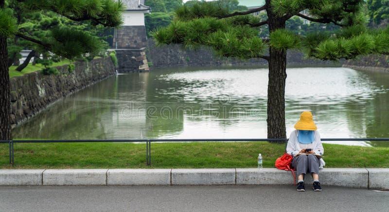 Mulher não identificada que senta-se pela lagoa do palácio imperial, Tóquio, Japão imagem de stock