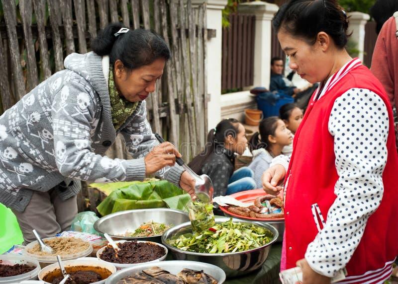 Mulher não identificada que vende o alimento no mercado asiático tradicional laos imagens de stock