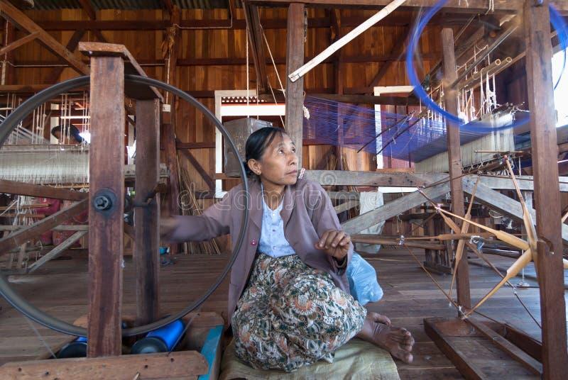 A mulher não identificada tecia a tela de seda pelo método e a máquina tradicional fotos de stock royalty free