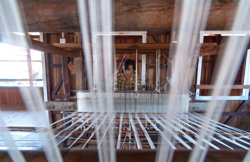 A mulher não identificada tecia a tela de seda pelo método e a máquina tradicional o 31 de dezembro de 2010, Inle, Myanmar fotos de stock