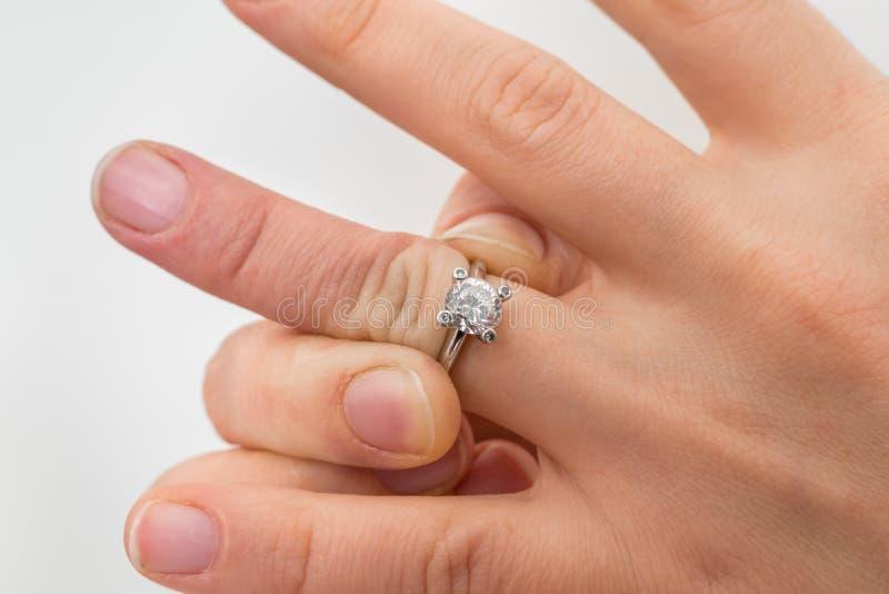 A mulher não pode decolar a aliança de casamento colada imagem de stock royalty free