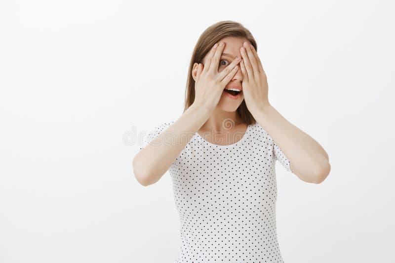 A mulher não pode esperar, querendo vê o que a espera, fechando-se eyes com as palmas, espreitando com o um olho através dos dedo fotografia de stock royalty free