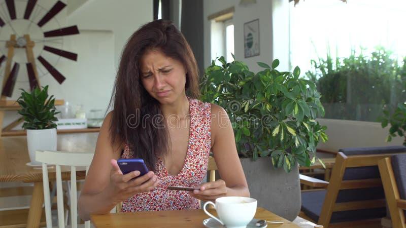 A mulher não pode fazer a compra com o cartão de crédito no telefone celular imagem de stock